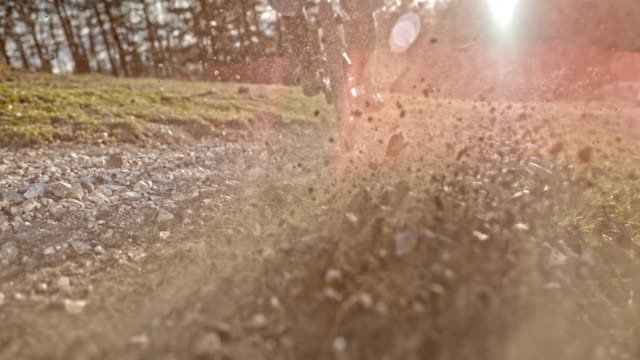 speed ramp mountain biker splashing gravel into the camera in sunshine - bike tire tracks video stock e b–roll