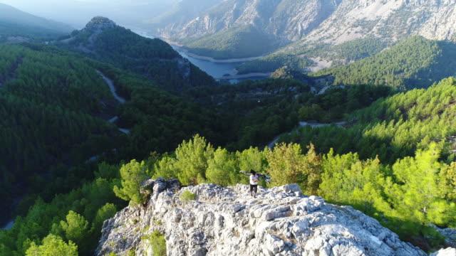 mountain biker standing on a rocky hillside - турция стоковые видео и кадры b-roll