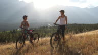 istock Mountain bikers converse on grassy ridge crest above valley 1269710555