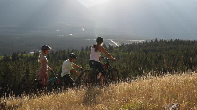 Mountain bikers converse on grassy ridge crest above valley