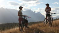 istock Mountain bikers converse on grassy ridge crest above valley 1269734764