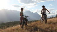 istock Mountain bikers converse on grassy ridge crest above valley 1269743195