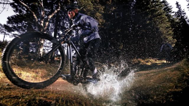 speed ramp mountain bikers che attraversano una pozzanghera forestale facendo un tuffo - andare in mountain bike video stock e b–roll