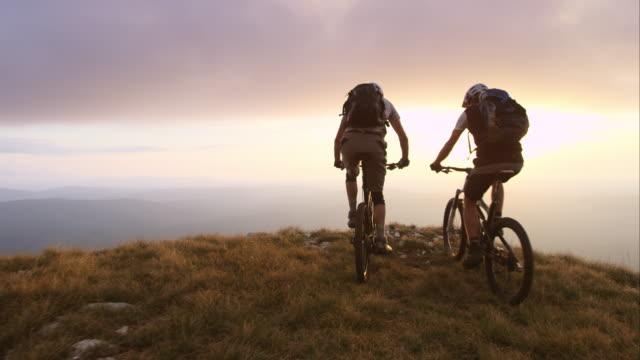 ts mountainbikecyklister att nå toppen i solnedgången och höja händerna - bergsrygg bildbanksvideor och videomaterial från bakom kulisserna