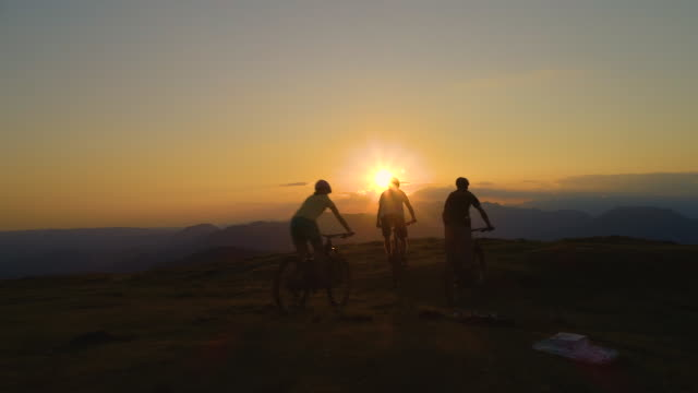 AERIAL: Mountain bikers ride up to end of grassy hill at sunrise and high five