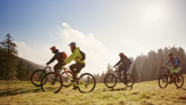 ts mountain bikers riding up a mountain across a meadow in sunshine - andare in mountain bike video stock e b–roll