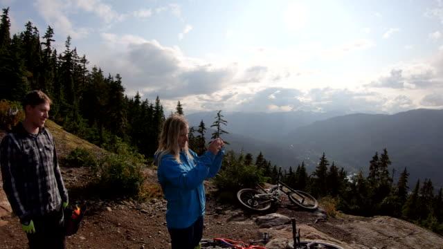 vídeos y material grabado en eventos de stock de los ciclistas de montaña toman la foto de un sendero alpino alto - memorial day weekend