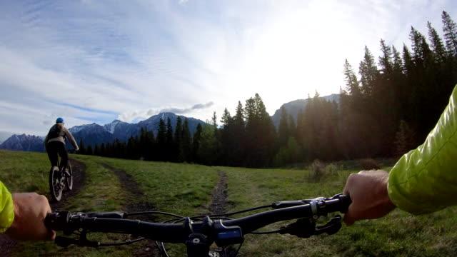 Mountain biking couple follow track through meadow, past fork