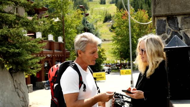 vídeos de stock, filmes e b-roll de o par biking da montanha faz a compra em linha com smartphone - camiseta preta