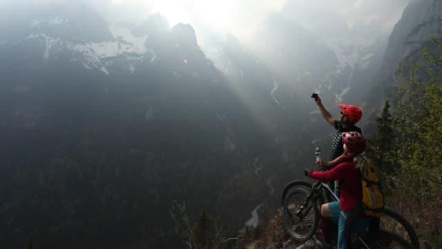 vídeos y material grabado en eventos de stock de par andar en bicicleta montaña pausa en el borde del precipicio, mirando de - memorial day weekend