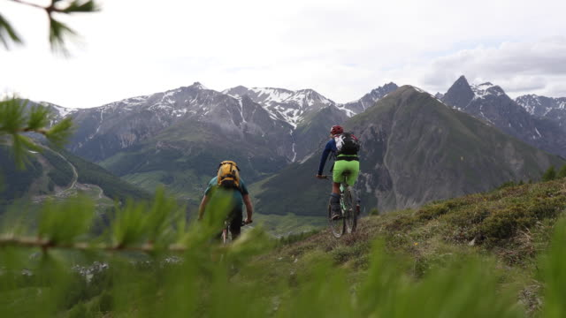 mountain biking friends venture across alpine meadow - pantaloni capri video stock e b–roll