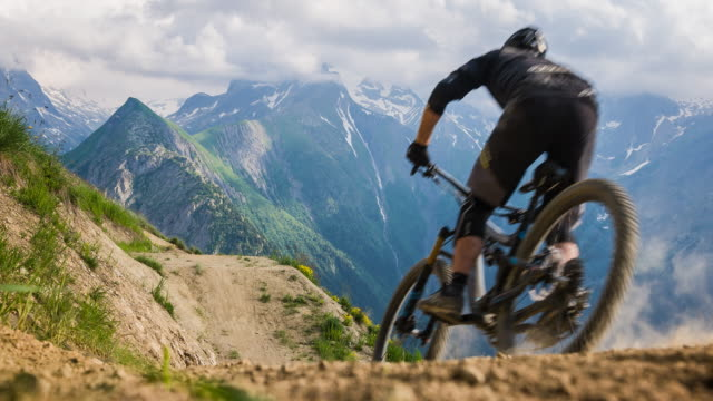 Mountain biking in mountain terrain, jumping Male mountain biker speeding downhill, jumping on dirt trail, performing the stunt called bike whip, mountain range in background horseback riding stock videos & royalty-free footage