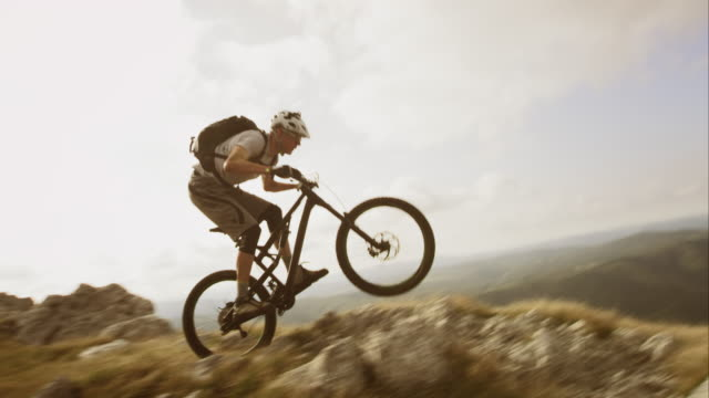 vídeos de stock, filmes e b-roll de ts slo mo mountain bike no rocky top - aventura