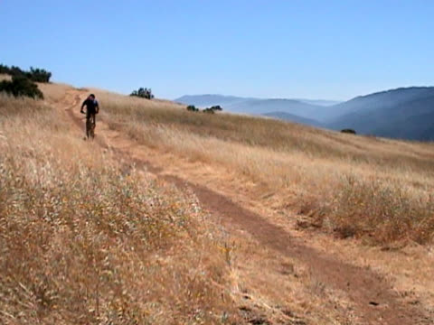 Mountain Biking The Coastal Range A mountain biker rides through a golden meadow on his way up a pacific coastal range trail.  Traveling alone, he looks like a serious sport rider out for a day trip.  Good natural tire and gravel sound. lockdown viewpoint stock videos & royalty-free footage