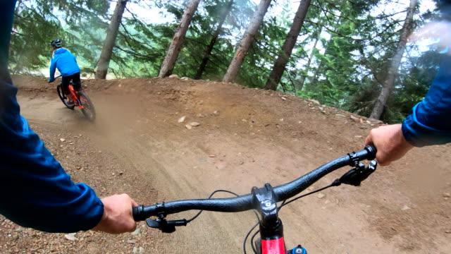 POV of mountain biking through forest on wet day