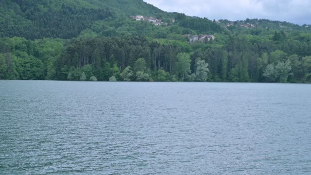 Mountain lake, forest and sky. Beautiful nature in a park reserve in the north of Italy. Calm atmosphere