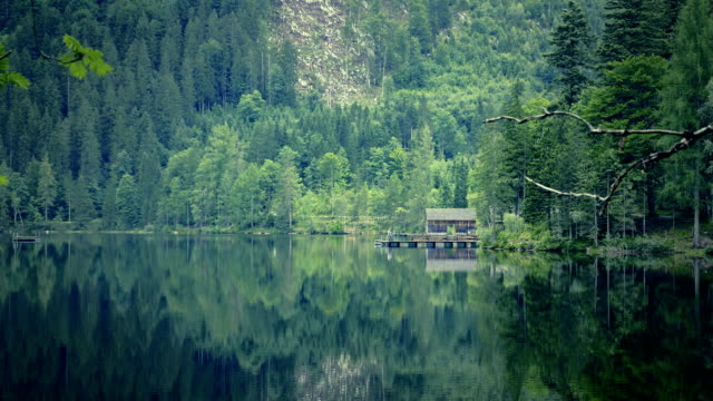Mountain lake with small wooden huts for fishing and swimming, wooden mist. video