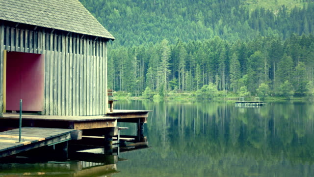 Mountain lake with wooden cabin hut for changing clothes, wooden mist, evening peaceful atmosphere. video