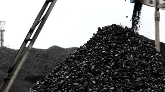 mountain of coal, coal falls from the conveyor Conveyor belt coal. Machine for loading coal. mining in coal mine coal stock videos & royalty-free footage