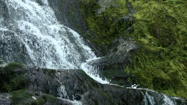 il fiume di montagna scorre sulle rocce. le gocce cadono su pietre ricoperte di muschio verde. la cascata gorgogliante forma schiuma e spray. trama di roccia ricoperta di lichene - acqua dolce video stock e b–roll