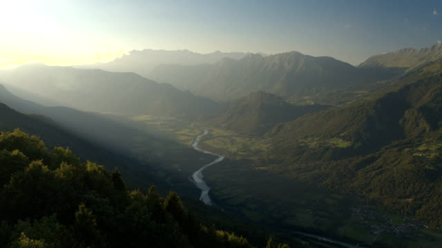 AERIAL: Mountain river running through beautiful green valley in misty evening video