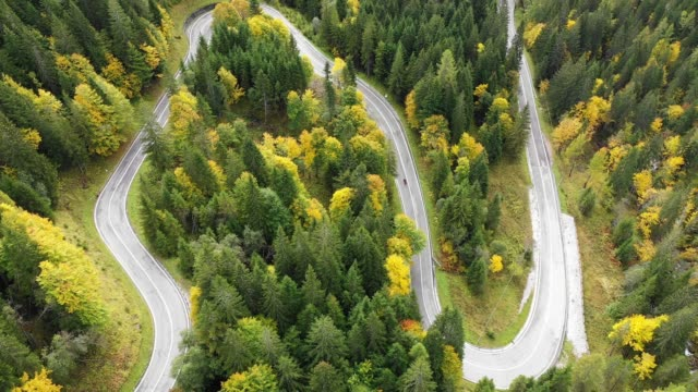 Mountain road serpentine. Italy, Dolomites. Aerial footage in autumn mountains. Serpentine road in the Dolomites, Alps, Italy. Dolomites mountain winding road, aerial view, Italy.