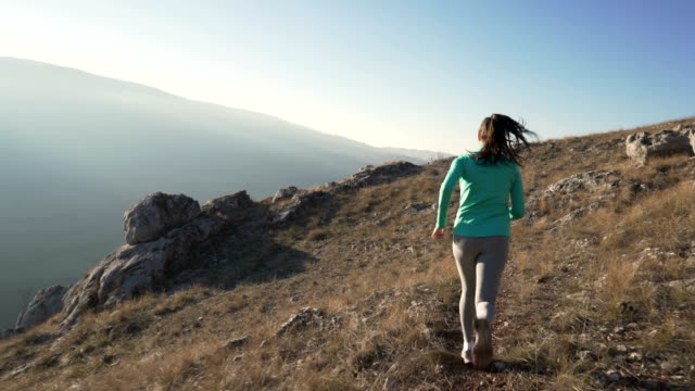 Mountain Running Rear view of a young woman jogging in nature. body care stock videos & royalty-free footage
