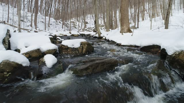 Mountain stream winter snow, low flying aerial