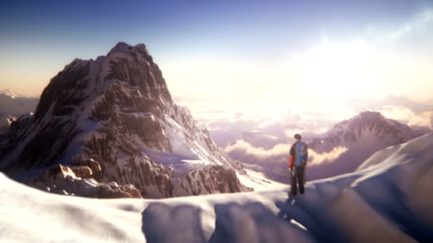 Mountain top with mountain climber Camera flies slowly past a peak with a climber - to reveal beautiful mountain. mountain stock videos & royalty-free footage