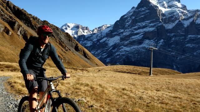 Mountainbiker steigt Hang mit dramatischen Blick hinter – Video