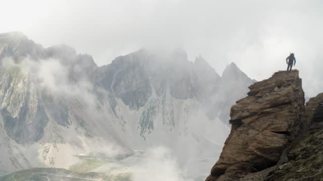 vídeos y material grabado en eventos de stock de un alpinista sube una pila de roca en un canto alto de la montaña como mal tiempo se cierra. - escalada en rocas