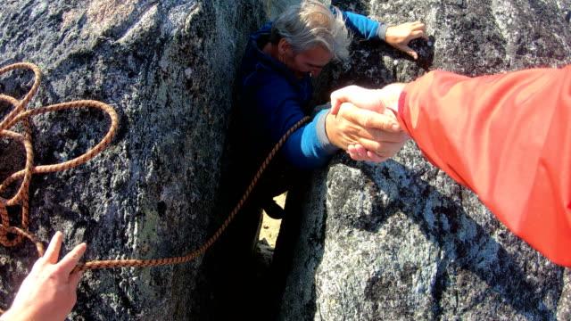 vídeos y material grabado en eventos de stock de mountaineer se prepara para ayudar a compañero de crack de alta montaña - escalada en rocas