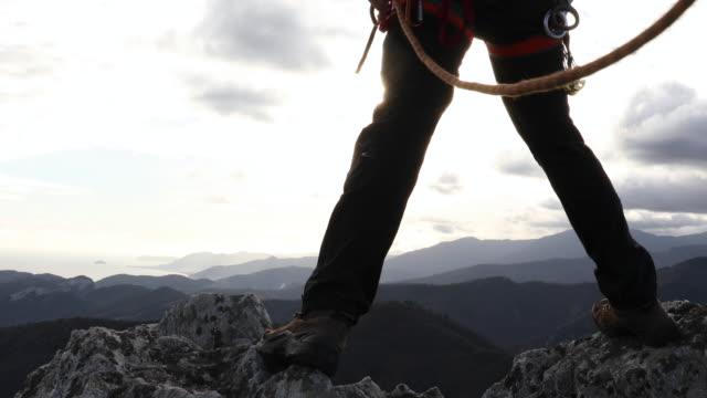 Bergsteiger erreicht Gipfel mit Blick auf Berge, Meer – Video