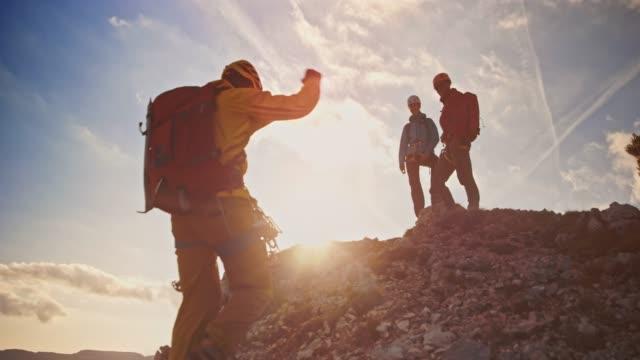 日差しの中で山の上で待機している仲間の登山と握手マウンテニアします。 - バックパッカー点の映像素材/bロール