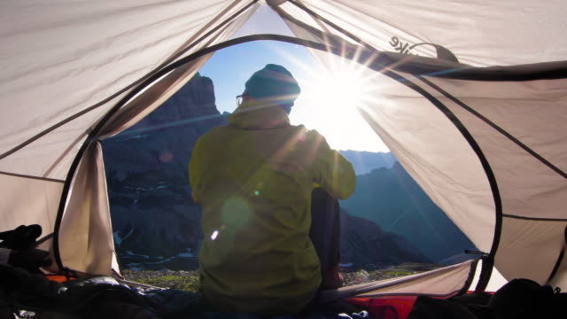 Mountaineer wakes up in tent at sunrise