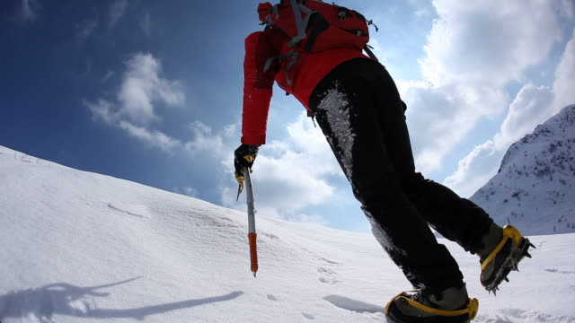 Mountaineer walking uphill along a snowy slope. HD1080P video