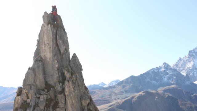 vídeos de stock e filmes b-roll de mountaineers ascends vertical rock pinnacle - 55 59 anos