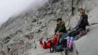istock Mountaineers enjoy lunch at base of climb 1264631180