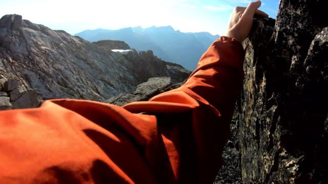 vídeos de stock, filmes e b-roll de as mãos do alpinista encontram a compra no pedregulho equilibrado que alcanga a parte superior - penedo