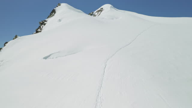 Mountaineers track leads across slope full of white snow upwards to mountain top