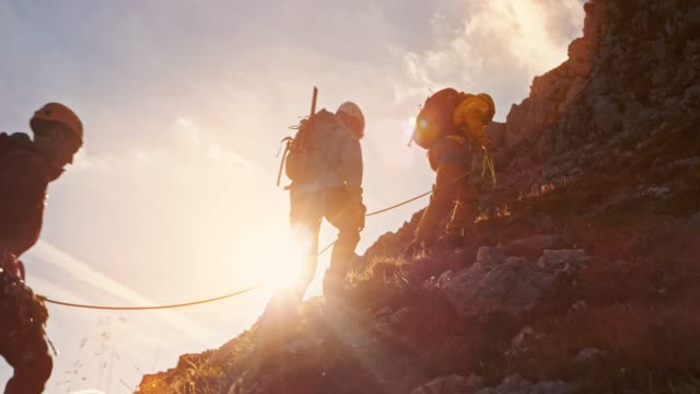 td mountaineers walking slowly towards the mountain top at sunset - tre persone video stock e b–roll
