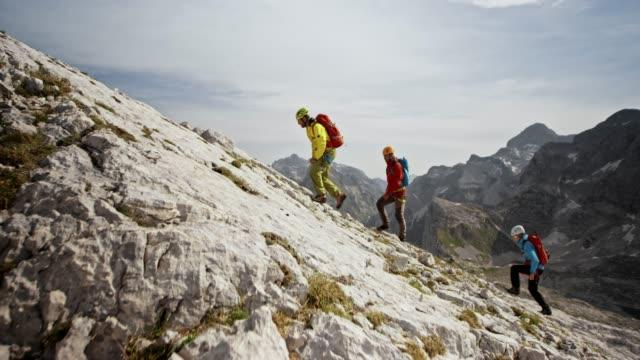 vídeos de stock, filmes e b-roll de alpinistas subindo uma encosta rochosa no sol - escalada