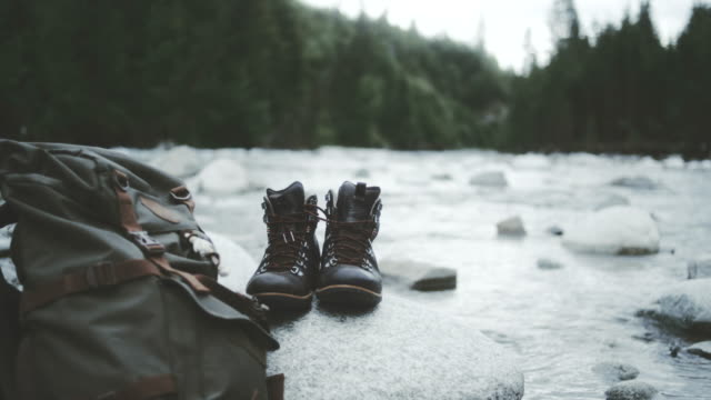 Mountainous landscape. Close up on hiking boots and backpack video