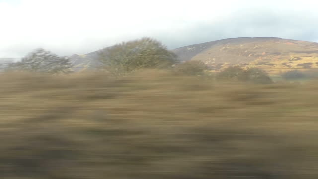 mountainous landscape of scotland through train window - wagon kolejowy filmów i materiałów b-roll