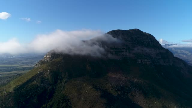 Mountains peaking through the clouds A large cloud covers the top of the Helderberg Mountain in Somerset West, Cape Town western cape province stock videos & royalty-free footage