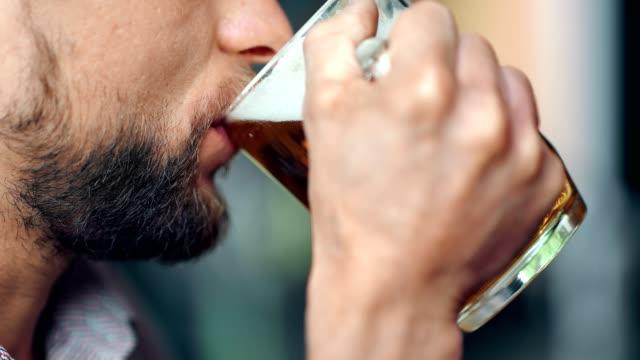 Mouth of mature European bearded man drinking cold dark fresh beer holding big glass mug