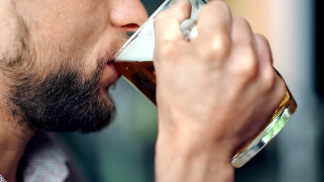 mouth of mature european bearded man drinking cold dark fresh beer holding big glass mug - baffo peluria del viso video stock e b–roll