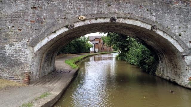 umzug nach vorne zeigt unter kanalbrücke, hinter baum ziegelhaus mit interessanten überhang. - landhaus stock-videos und b-roll-filmmaterial