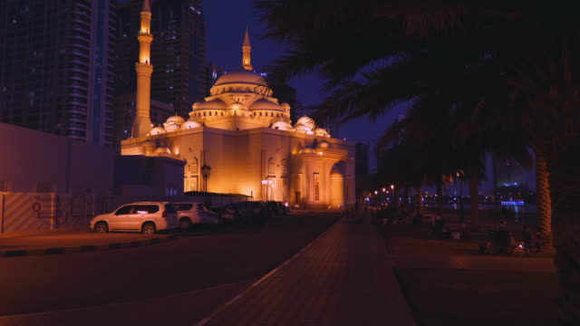 move the camera to a beautifully lit mosque at night along the alley. - eid mubarak stock videos and b-roll footage