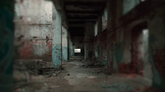Movement along corridor of ruined abandoned eerie pillar industrial building with blurred vignette video